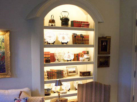 A Classic cabinet lighting fixture adds drama to the decor while showcasing prized books or art.